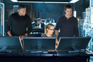 "Original Team Arrow Arrow -- ""Three Ghosts"" -- Image AR209b_0397b -- Pictured (L-R): David Ramsey as John Diggle, Grant Gustin as Barry Allen, Emily Bett Rickards as Felicity Smoak, and Stephen Amell as Oliver Queen, -- Photo: Diyah Pera/The CW -- © 2013 The CW Network, LLC. All Rights Reserved"